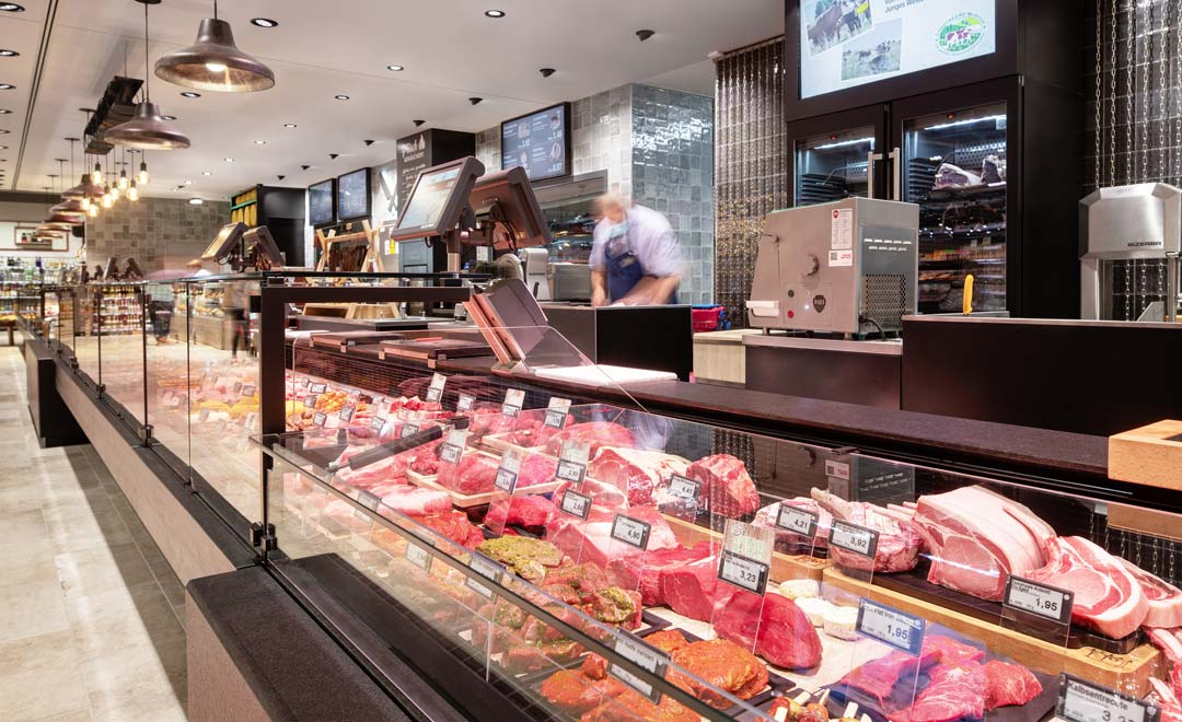 Fresh food counter for meat and sausage products, illuminated with Agira Plus recessed luminaire and Limba suspended luminaire.